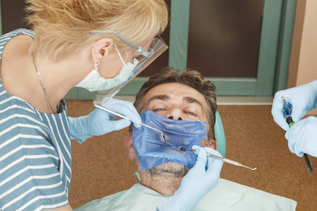 Patient at the dentist with a rubber dam