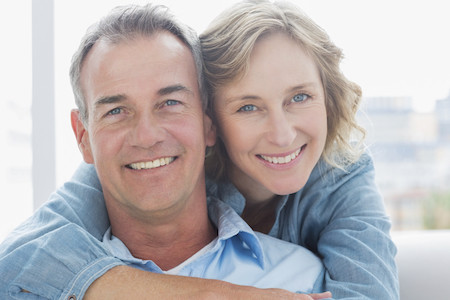 Smiling woman hugging her husband on the couch from behind at home in the living room
