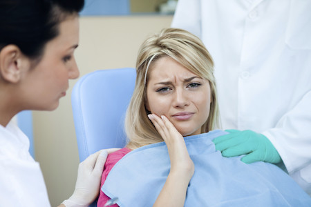 woman at the dentist in pain from wisdom teeth.